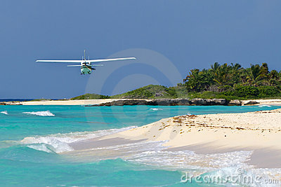 Tourist plane flying over Caribbean beach