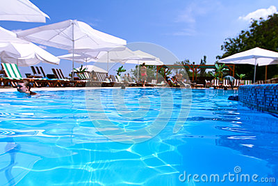 Tourist resort with pool, white parasols and people