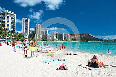 Tourist sunbathing and surfing on the Waikiki beach in Hawaii. Editorial Stock Image