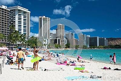 Tourist sunbathing and surfing on the Waikiki beach in Hawaii. Editorial Image