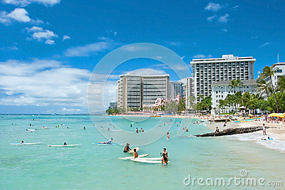 Tourist sunbathing and surfing on the Waikiki beach in Hawaii. Editorial Photography