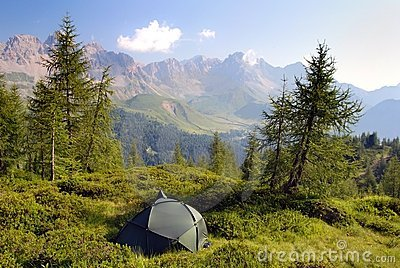 Tourist tent in the green forest on mountains