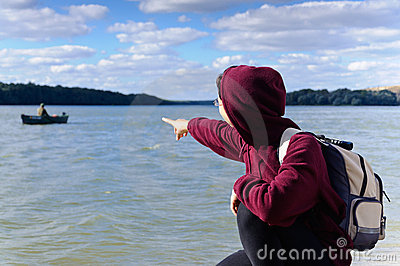 Tourist woman pointing at fishing boat