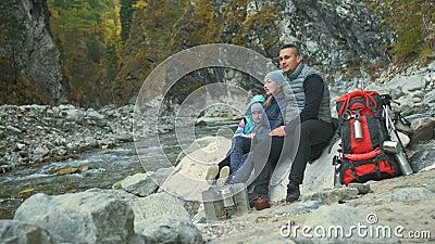 Touristen ruhen nach einer Wanderung Familienreisen Umwelt durch Berge, Flüsse, Bäche Eltern und Kinder gehen stock video