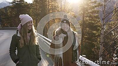 Touristes positives en manteaux d'hiver marchant au ralenti sur une longue route à travers la campagne vers la neige banque de vidéos