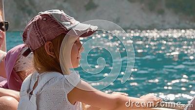 Touristique voyageant en bateau à voile en croisière en mer Jeune fille assise à bord d'un voilier en voyage en mer au soleil banque de vidéos