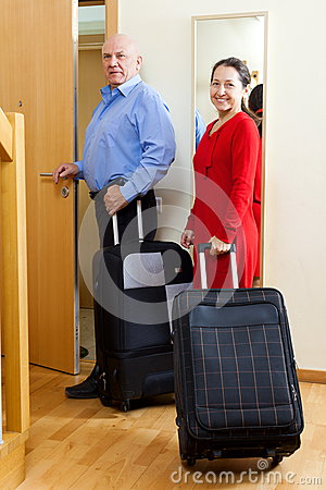 Tourists with baggage near door in home