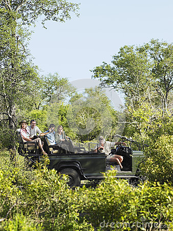 Tourists And Driver In Jeep On Safari