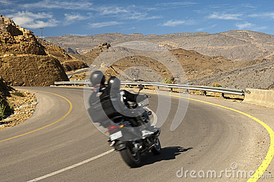Tourists driving on a motor-bike in a curve