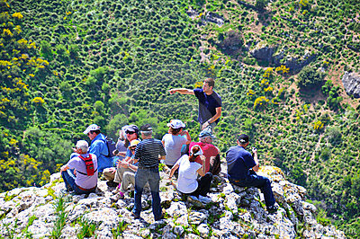 Tourists and guide on cliff edge, Israel Editorial Stock Photo
