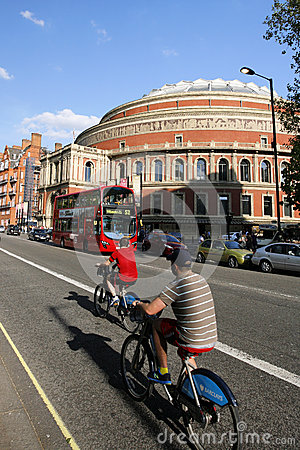 Tourists on rental bike, passing by Royal Albert Hall Editorial Photo