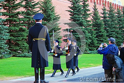 Tourists taking photos of marching soldiers Editorial Stock Image