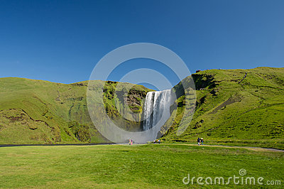 Tourists walking near famous Skogafoss waterfall, South Iceland