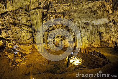 Tourists walking on stalactites cave looking infernal