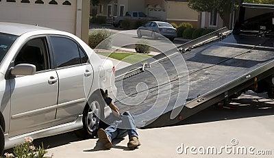 Tow-truck picking up broken down car