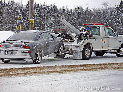 wrecker towing a car in winter