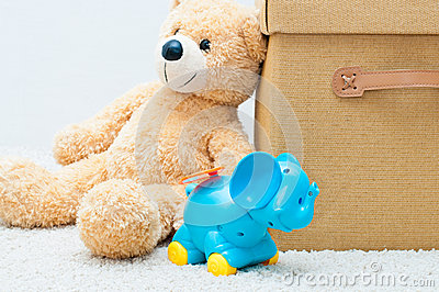 Toy bear and clockwork elephant with brown textile box with hand