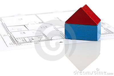 Toy block house on blueprint of floor plan