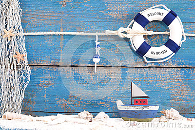 Toy boat with shells on a blue wooden background for summer, hol