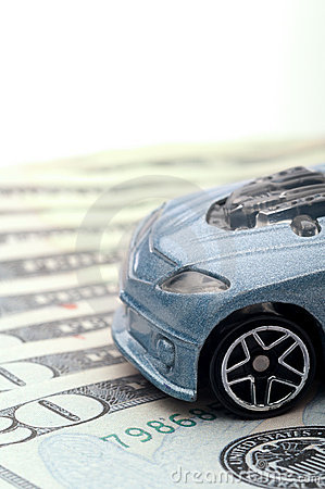 Toy car sitting on currency: new car loan