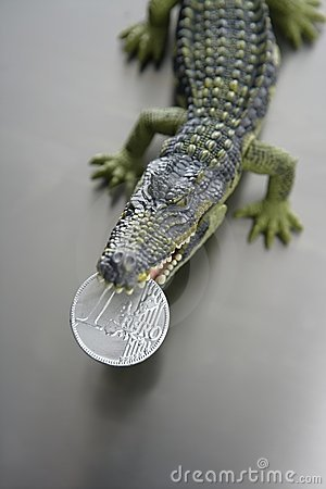 Toy cocodrile, aligator with one euro coin in jaws