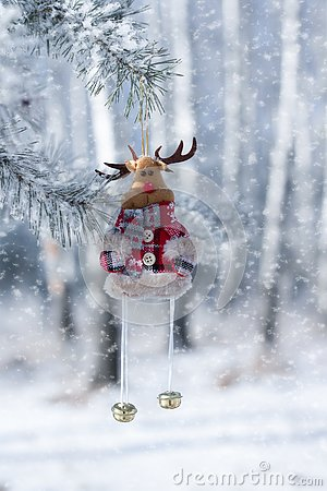 Toy deer with bells, Christmas decoration, close-up, against the winter forest, where snow falls Stock Photo