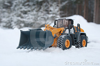 Toy heavy bulldozer on the snow
