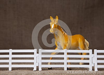 Toy horse behind fence