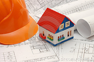 Toy house model on blueprints with helmet near by