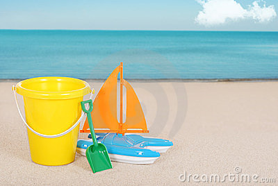 Toy Sailboat and childs bucket on the beach