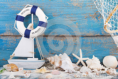 Toy sailboat and life buoy with seashells and starfish an a wood