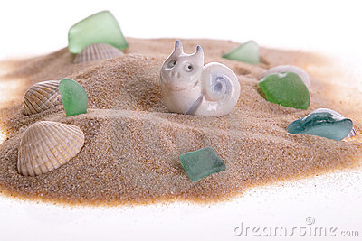 Toy snail on sand near cockles and stones