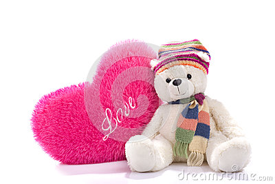 Toy teddy bear sitting with heart-shaped pillow