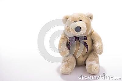 Toy teddy bear wearing bow-tie