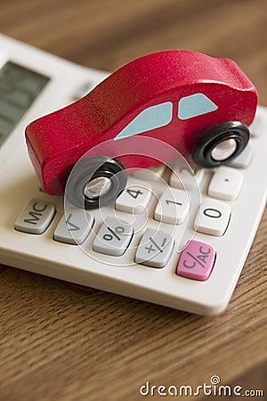 Toy Wooden Car On Calculator vermelho para ilustrar o custo de viajar de automóvel