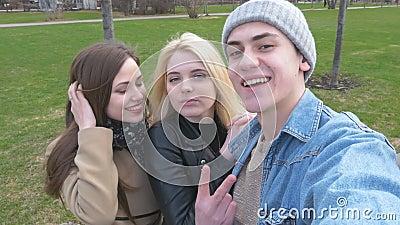 Três amigos, fazem o selfie para uma caminhada no parque Louro, morena e um homem novo Tenha o divertimento e aprecie a vida vídeos de arquivo