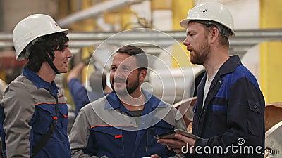 Três coordenadores dos amigos na fábrica da indústria pesada, sorriso e discutem planos video estoque