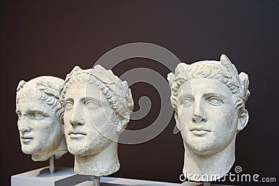 Três esculturas masculinas das cabeças no estilo do grego clássico