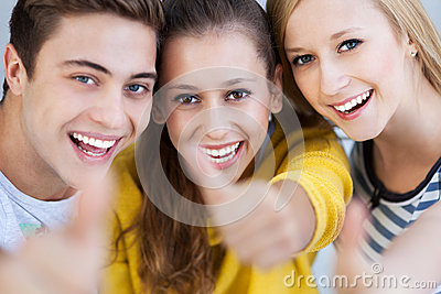 Três jovens com polegares acima