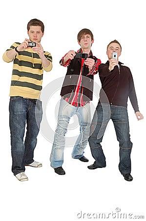 Três meninos que disparam em algo no telefone móvel