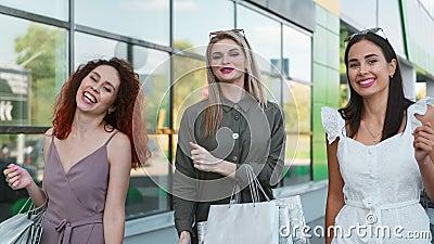 Três moça bonita sorrindo dançando ao ar livre em vidro de janela vídeos de arquivo
