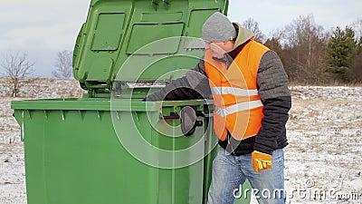 Trabajador con los bolsos de basura cerca del envase en invierno metrajes