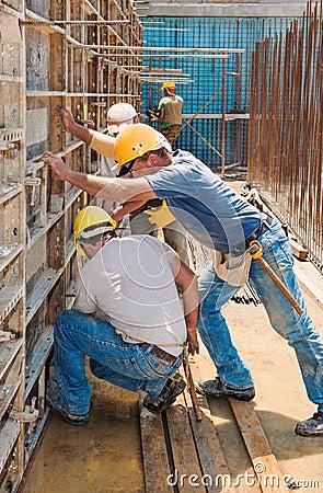Trabajadores de construcción ocupados con los marcos del encofrado