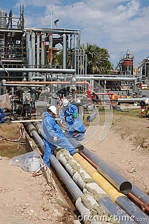 Trabajadores de la refinería de petróleo Foto editorial