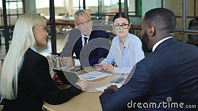 Trabajadores de oficina negociando en sala de reuniones, oferta de negocios, acuerdo de asociación metrajes