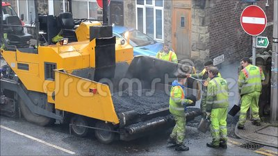 Trabajadores del camino que reparan la superficie de la carretera metrajes