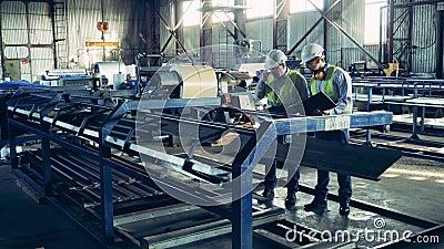 Trabajadores observan un transportador de fábrica con herpes de metal almacen de video