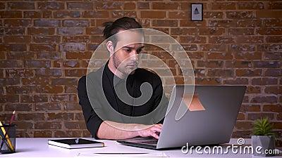 Trabalhador caucasiano concentrado que texting em seu portátil, centrado sobre seu trabalho tat a tabela interna filme