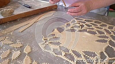 Trabalhador cortando pedaços de massa com cortador de biscoitos video estoque