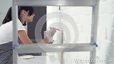 Trabalhador de mulher que usa paredes de pintura de uma escova no apartamento ou na casa Constru??o, reparo e renova??o filme